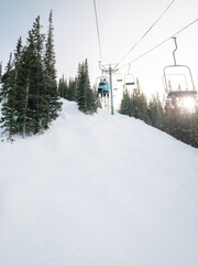 Chairlift in winter, two kids on chair, viewed from behind