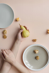 Pear In Hand And Ground Cherries On Table