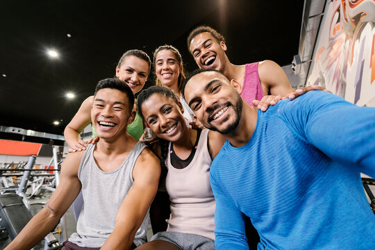 Interracial gym partners taking a selfie after workout at gym.