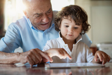 2 year old boy with his grandfather using a digital tablet