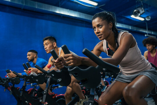 Group of sporty people training on exercise bikes together at gym.
