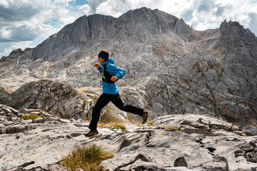 Trail runner jumping on rocky scenery on cloudy day