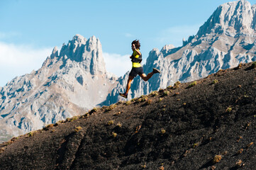 Runner running with big strides and jumping downhill in Picos de Europa National Park
