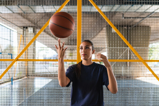 woman with a basket ball spinning on her finger.