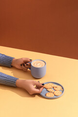 Holding warm coffee and eating cookies. Woman hands
