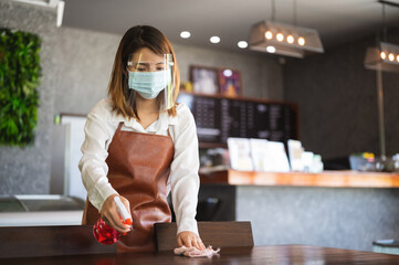 New normal startup small business Portrait of Asian woman barista wearing protection mask and face shield cleaning table in coffee shop while social distancing