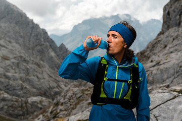 Trail runner drinking water on a rainy day close to gray limestone mountains