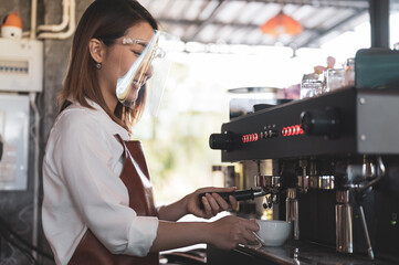 Close up image of barista wearing faceshield preparing coffee at cafe while social distancing new normal life