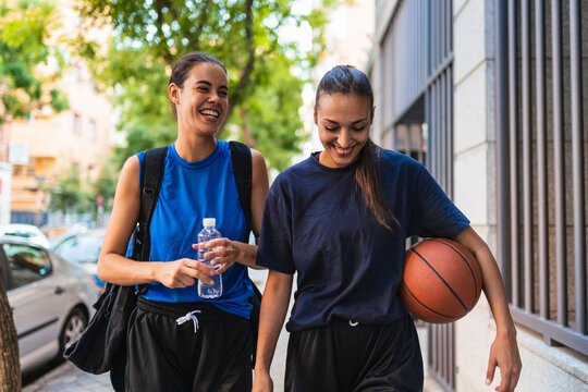 Two women basketball players laughing