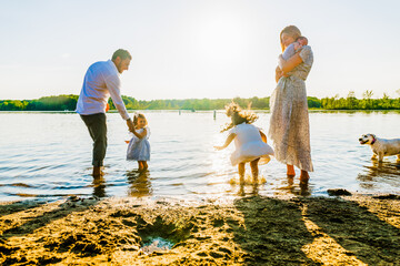 Family playing on the shore of a lake in summer