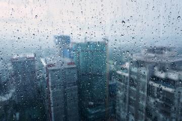 Obraz Buildings Seen Through Wet Glass Window During Rainy Season - fototapety do salonu