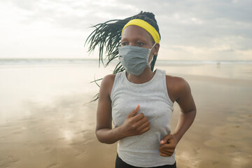 new normal beach running workout of African American woman - young attractive and athletic black...