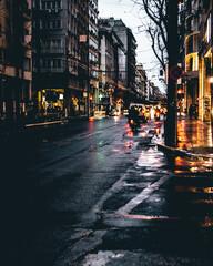 Fototapeta Wet Street Amidst Buildings In City During Rainy Season obraz
