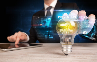 Businessman holding lightbulb with FRAUD PREVENTION inscription, online security idea concept