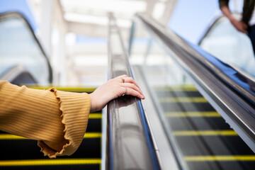 エスカレーターを登る女性の手元