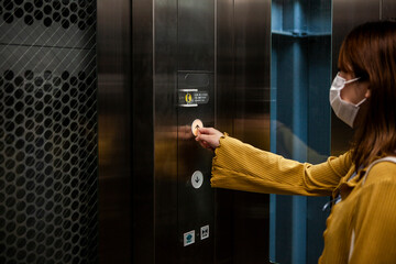 エレベーターのボタンを慎重に押す女性