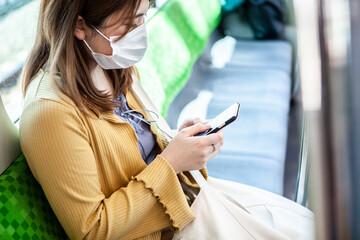 マスクをして電車に乗る女性