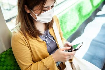マスクをして電車に乗りスマートフォンを操作する女性