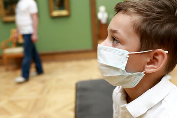 Child wearing medical protection mask in picture gallery
