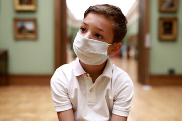 Child wearing protection mask in art gallery