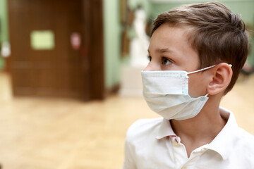 Kid wearing medical protection mask in picture gallery