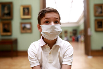 Kid wearing protection mask in art gallery