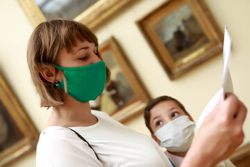 Mother with son wearing protection mask in museum