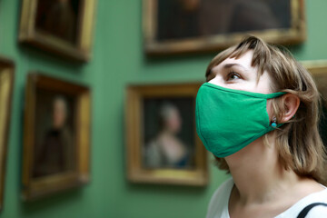 Woman wearing protection mask in picture gallery