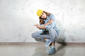 Beautiful female hip-hop dancer against light wall