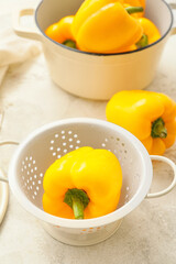 Yellow bell pepper in colander on table