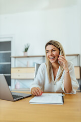 Smiling woman talking on smart phone while sitting in cozy office, portrait.