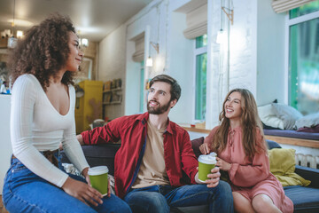 Girl and guy looking at curly girlfriend drinking coffee couch