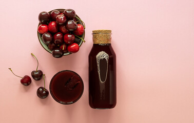 Tuinposter Sap Cold cherry juice in a glass and bottle with ripe berries
