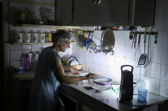 Samira Hanna, 70, washes dishes in her kitchen as she uses a portable electric light due to a power cut, in Beirut