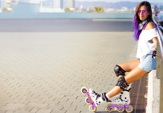 Roller skating young Caucasian girl with violet hair, sunglasses and protection outdoors sitting on parapet and relaxing after rollerblading on inline skates. outdoor summer activities. Space for text