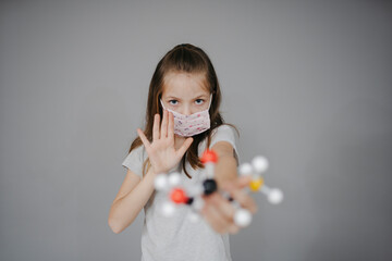 Photo sur Toile Les Textures beautiful young girl with nose mouth mask is holding molecule model during corona time
