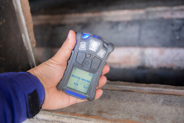 Obraz Inspector using the portable gas detector for detect combustible gas , flammable gas , toxic gas and oxygen depletion in a confined spaces before starting work. - fototapety do salonu