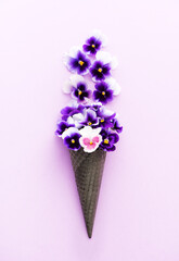 Poster Pansies Healthy life concept. Edible flowers pansies viola in a waffle cone on lilac background, Flat lay