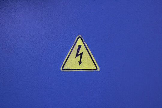 Yellow electricity sign on a blue wall