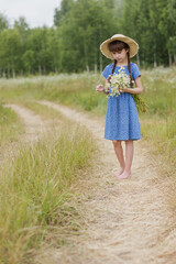 Photo sur Plexiglas Doux monstres 10 years old barefoot girl with flowers in summer day