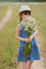 Photo sur Toile Doux monstres portrait of cute little girl in a hat holding chamomiles bunch on the field
