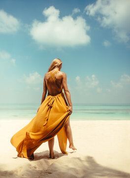 Rear view of young woman in yellow dress walking on beach