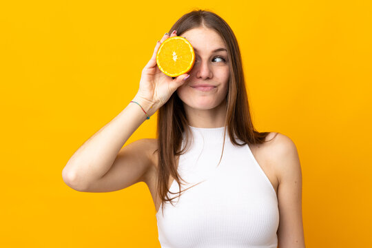 Young caucasian woman holding an orange isolated on orange background
