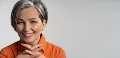 Mature woman broadly smiling with fingers crossed. Happy female model in orange shirt. Close up...