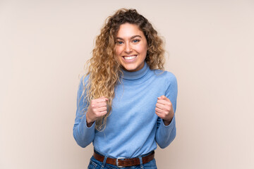 Young blonde woman with curly hair wearing a turtleneck sweater isolated on beige background...