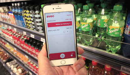 An app on a mobile phone shows to a client the price of a product after scanning the barcode at an avec box convenience store in Zurich
