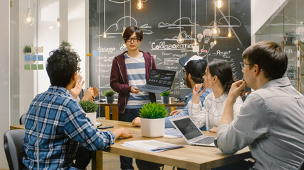 Charismatic Asian Team Leader Shows Laptop with Data Statistics to Diverse Group of Talented Young Developers, They Start Discussion at Meeting Table. Creative People in Stylish Office Environment.