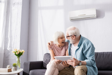 Senior man holding digital tablet and embracing smiling wife on couch