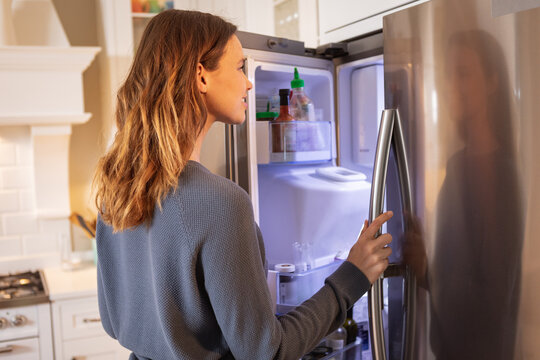 Woman opening the fridge at home
