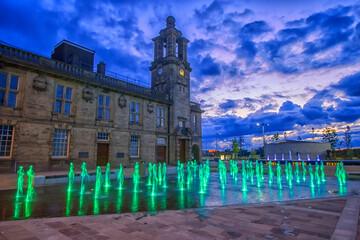 Fotomurales - Illuminated Human Fountains Outside Historic Building At Dusk